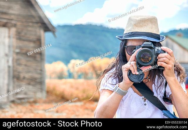 Woman wearing straw hat making pictures of mountain landscpae with wooden hut
