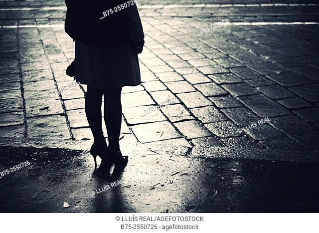 Backlight silhouette of an unrecognizable woman with stiletto heel shoes, standing up on the sidewalk of a street Milan, Italy, Europe