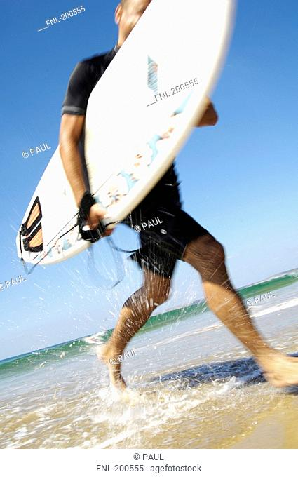 Man running with surfboard on beach