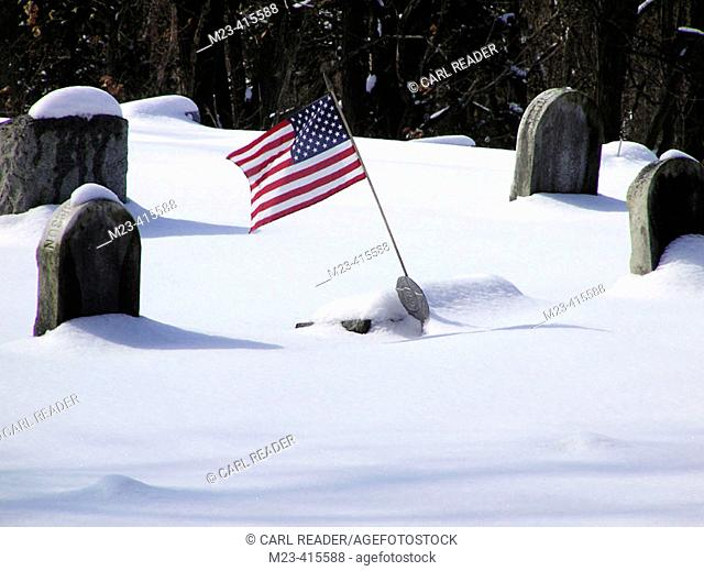 An American flag flies over colonial graves covered in snow