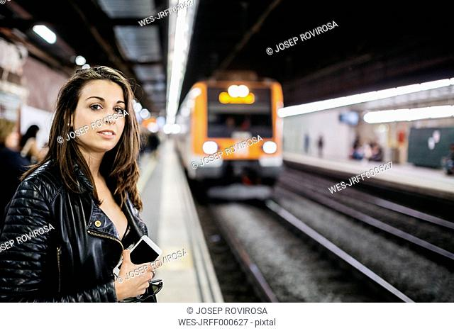 Young woman on train station awaiting train coming in