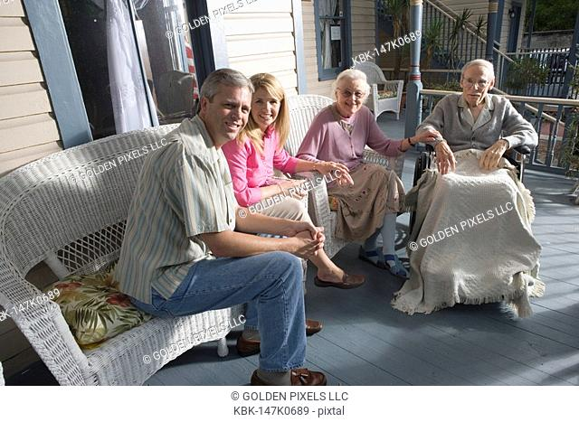Family with elderly parents and adult children sitting together on front porch