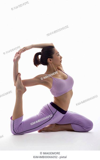 Woman practicing yoga and looking away with feet up