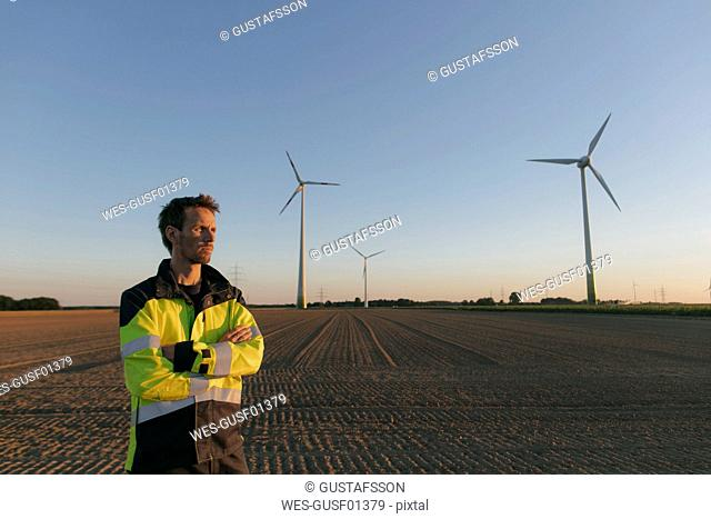 Engineer standing in a field at a wind farm