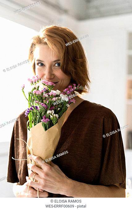 Redheaded woman smelling bunch of flowers