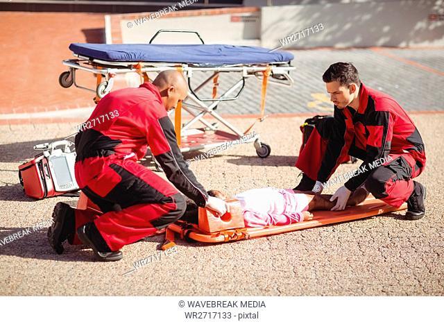 Paramedics putting injured girl onto a backboard