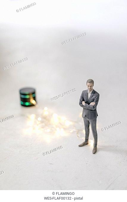Miniature businessman figurine standing next to smart home loudspeaker with chain of lights