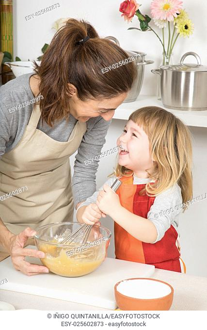happy tender scene: woman with glass bowl, and three years old child looking smiling and whipping with whisk, in teamwork, cooking a sponge cake at kitchen home