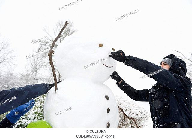 Man and woman building snowman together