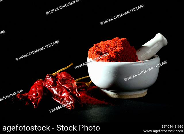 Red Chili Pepper powder in pestle with mortar and Red Chili Peppers on black background