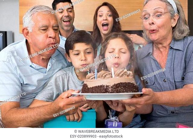 Extended family blowing candles on cake in living room