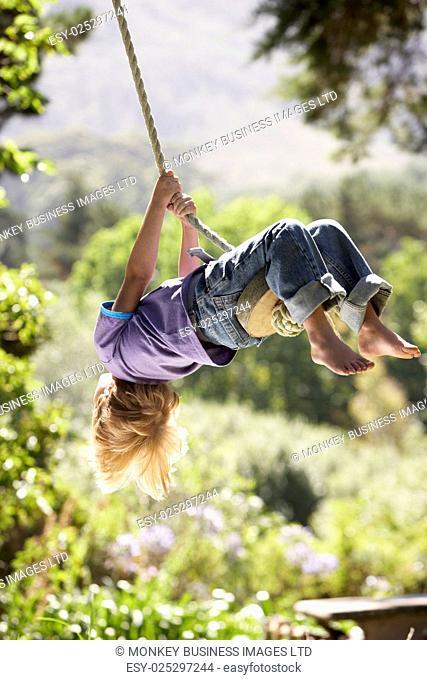 Young Boy Having Fun On Rope Swing
