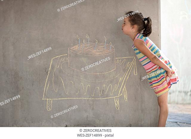 Girl pretending to blow out chalk birthday cake and candle drawing on concrete wall