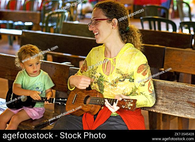 Mother and daughter playing ukelele in Polynesian Cultural Center. O'ahu. Hawaii. The Polynesian Cultural Center (PCC) is a Polynesian-themed theme park and...