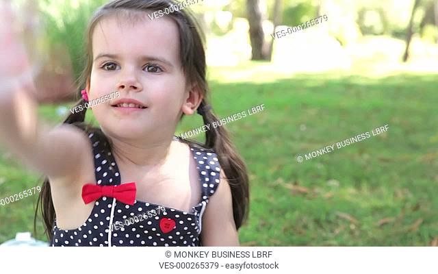 Girl sits on rug in countryside and tries to catch bubbles blown in from out of shot.Shot on Canon 5D Mk2 at at a frame rate of 30 fps