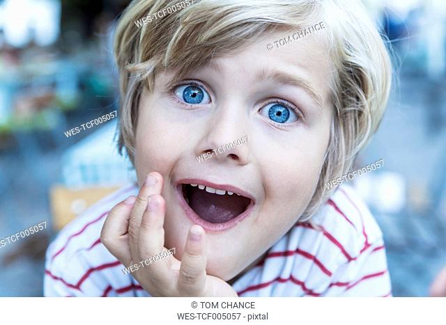 Portrait of little blond boy with eyes wide open and open mouth