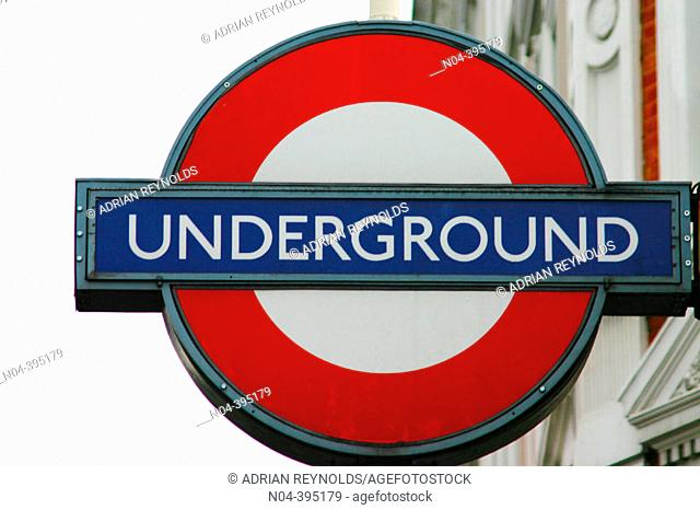 A sign for the London subway in front of a building. London. England