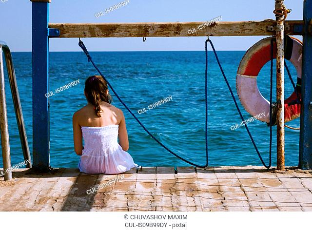 Rear view of girl sitting on pier looking out to sea