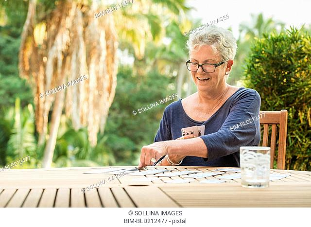Caucasian woman playing cards outdoors