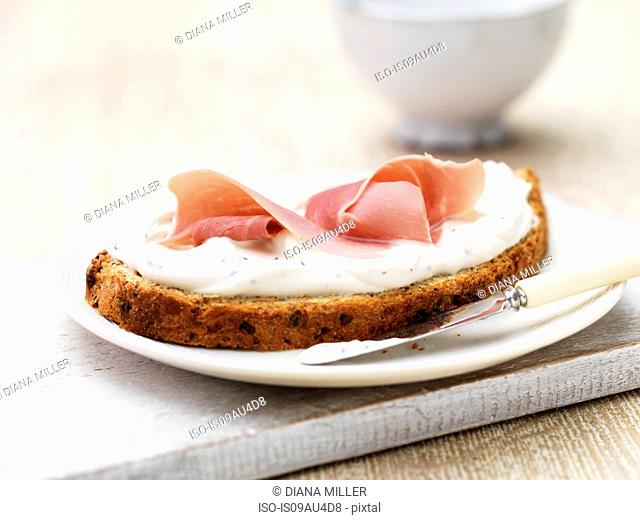 Soft cheese and ham on sliced wholemeal bread with butter knife