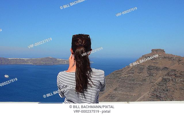 Santorini Greece young woman taking video with Iphone on holiday having fun on cliff in Fira Greek vacation 13