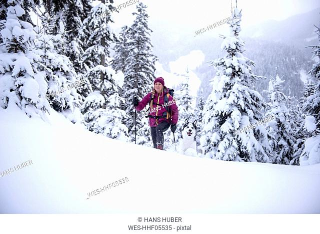 Austria, Altenmarkt-Zauchensee, young woman with dog on ski tour in winter forest
