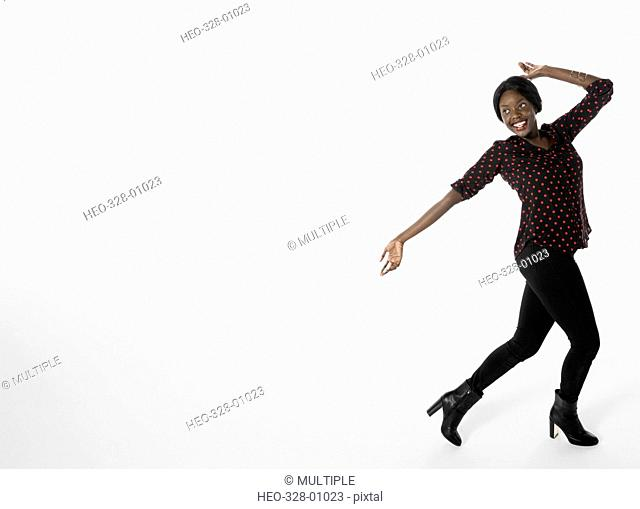 Portrait happy, playful businesswoman dancing against white background