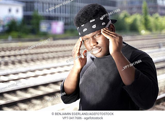 African teenage man in train station with fingers on temples. Munich, Germany