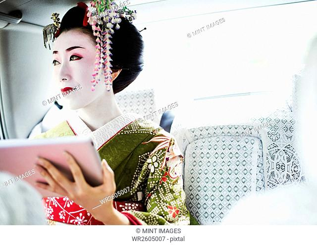 A woman dressed in the traditional geisha style, wearing a kimono with an elaborate hairstyle and floral hair clips, with white face makeup holding a digital...