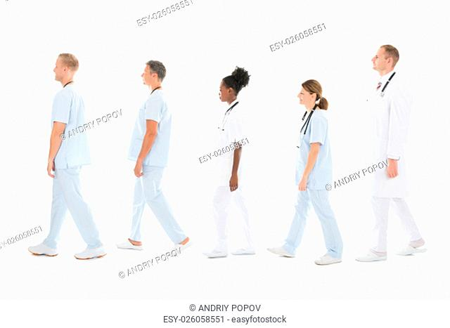 Full length side view of medical team walking in row against white background