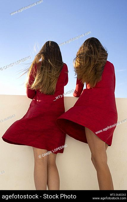 Two young girls with red dresses and long blonde hair at the wind