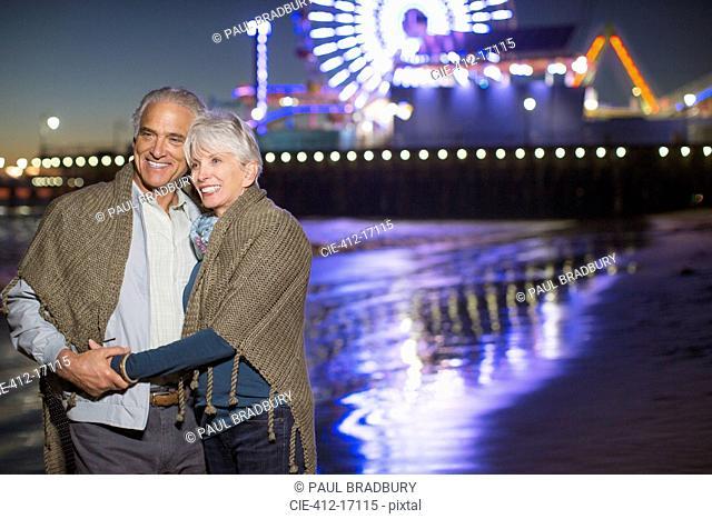 Senior couple hugging on beach at night