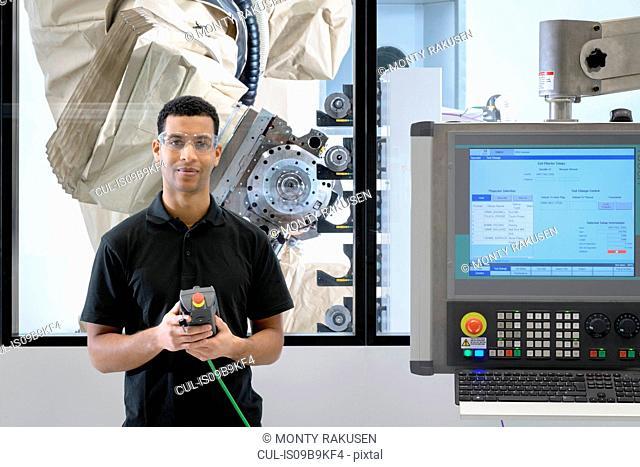 Portrait of apprentice robotics engineer with robot in robotics research facility