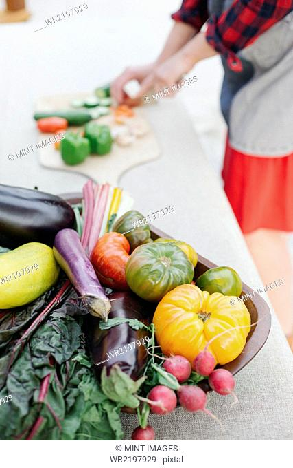 Wooden bowl with fresh vegetables standing on a table