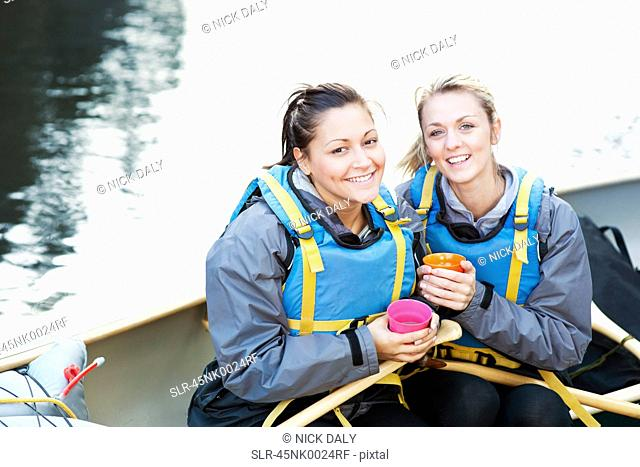 Women having coffee in canoe