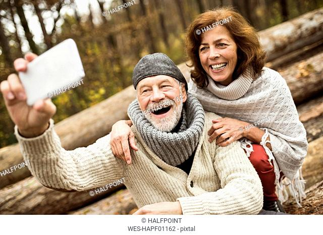 Portrait of laughing senior couple taking selfie with cell phone