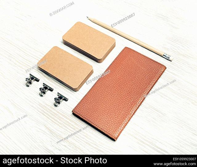 Blank notepad, kraft business cards and pencil on light wood table background. Photo of blank stationery set