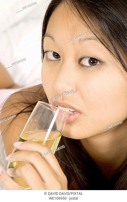 Model Release 288 Asian woman in early 20's laying in bed drinking white wine
