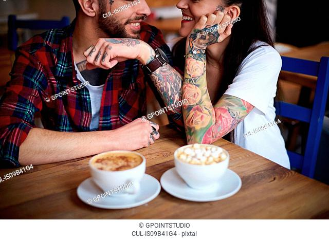 Couple in coffee shop face to face smiling