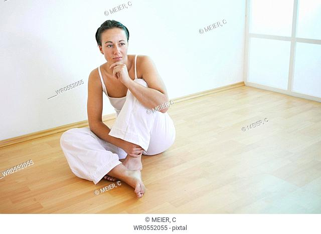 Young woman sits with tucked up leg on the floor, her chin rests on her left hand