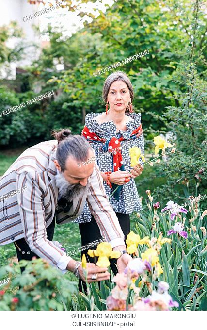 Couple picking flowers from garden