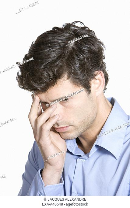 Contemplative young man with hand on face