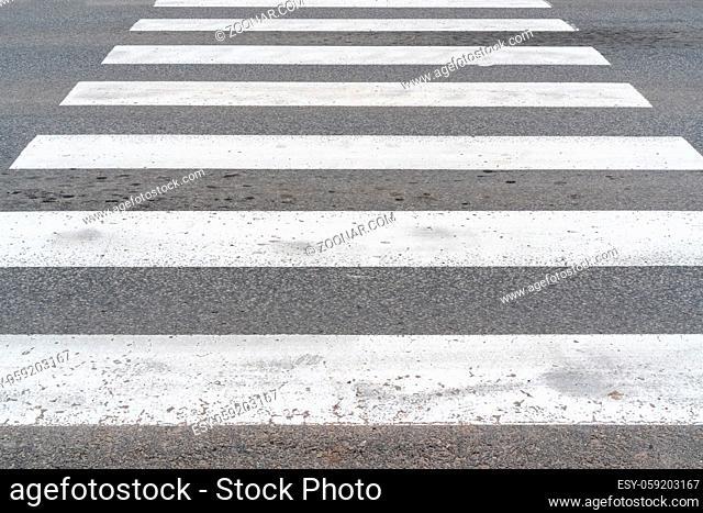 White crosswalk on asphalt. Road marking pedestrian crossing close-up