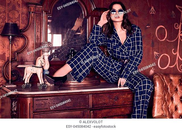 Portrait of a beautiful elegant brunette woman dressed in a blue checkered suit in a luxury antique interior