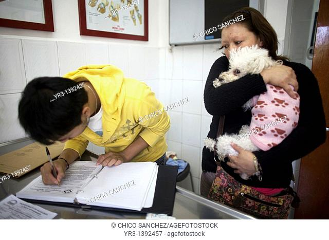 A man signs permission to put his Poodle dog in the hospital as his mother holds it at a Pet Hospital in Condesa, Mexico City, Mexico, February 2, 2011