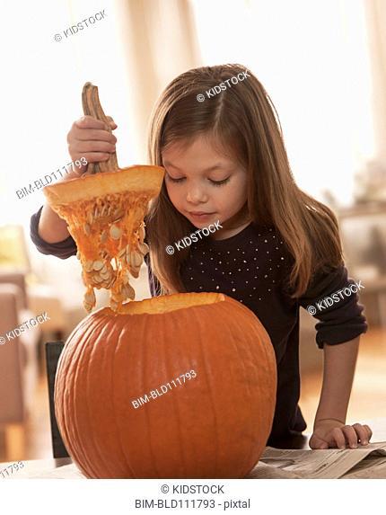 Caucasian girl carving pumpkin at table