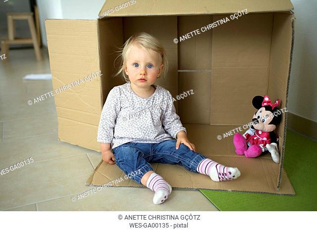 Portrait of little girl sitting on the floor of children's room in front of cardboard box