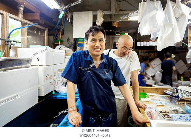 A traditional fresh fish market in Tokyo. Two men in aprons working on a fresh produce stall