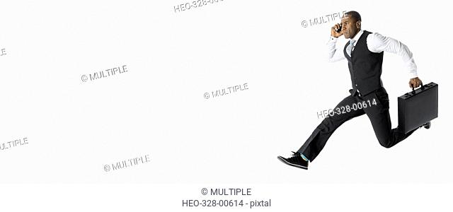 Energetic businessman running and jumping, talking on cell phone against white background