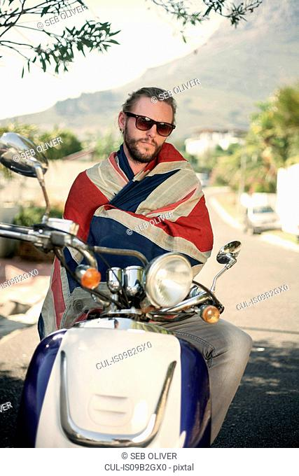 Portrait of man wrapped in union jack sitting on moped, Cape Town, South Africa